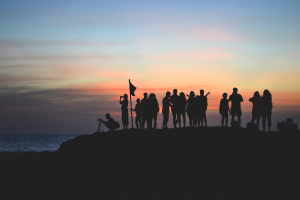 A group of people on a mountain, silhouetted.